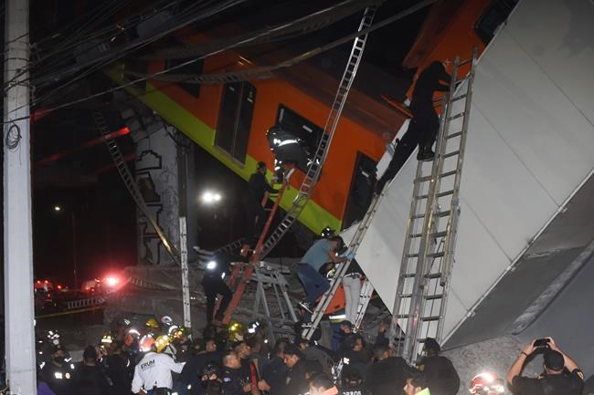 Mexico City fire fighters and rescue personnel work to recover victims from a subway car that fell after a section of Line 12 of the subway collapsed in Mexico City, Monday, May 3, 2021. The section passing over a road in southern Mexico City collapsed Monday night, dropping a subway train, trapping cars and causing at least 50 injuries, authorities said. (AP Photo/Jose Ruiz)