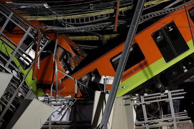 Mexico City's subway cars lay at an angle after a section of Line 12 of the subway collapsed in Mexico City, Tuesday, May 4, 2021. The section passing over a road in southern Mexico City collapsed Monday night, dropping a subway train, trapping cars and causing at least 50 injuries, authorities said. (AP Photo/Marco Ugarte)