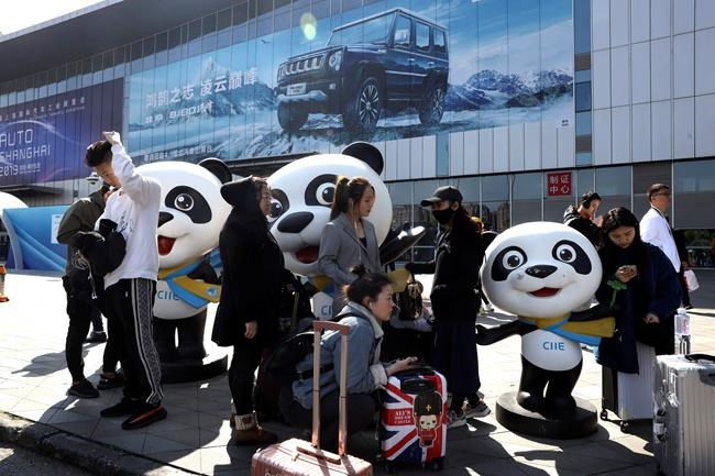 Workers wait to enter the venue for the Auto Shanghai 2019 show in Shanghai on Monday, April 15, 2019. This year's Shanghai auto show which starts Thursday highlights the global industry's race to make electric cars Chinese drivers want to buy as Beijing winds down subsidies that promoted sales. (AP Photo/Ng Han Guan)