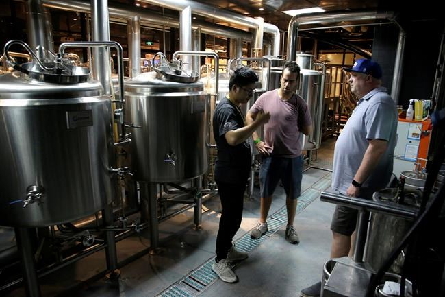 In this Thursday, May 17, 2018, photo, Michael Jordan, right, talks to staff at the small-batch brewery run by Boxing Cat Brewery inside the Liquid Laundry gastropub in Shanghai. Hundreds of craft beer enthusiasts, investors and brewers are attending an exhibition in Shanghai dedicated to expanding the palette of Chinese consumers and promoting sales of high-end brews. (AP Photo/Sam McNeil)