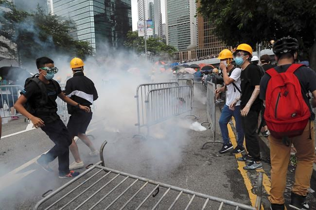 Protestors react to tear gas during a large protest near the Legislative Council in Hong Kong, Wednesday. (Kin Cheung / The Associated Press)