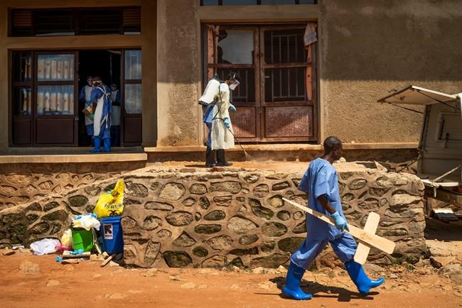 In this photograph taken Sunday July 14, 2019, a morgue employee walks with a cross past others disinfecting the entrance to the morgue in Beni, Congo DRC. The head of the World Health Organization is convening a meeting of experts Wednesday July 17, 2019 to decide whether the Ebola outbreak should be declared an international emergency after spreading to eastern Congo's biggest city, Goma, this week. More than 1,600 people in eastern Congo have died as the virus has spread in areas too dangerous for health teams to access. (AP Photo/Jerome Delay)
