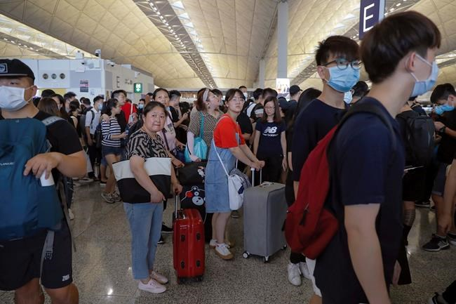 A group of travelers, center, is surrounded by protesters during a protest at the Hong Kong International Airport, Monday, Aug. 12, 2019. One of the world's busiest airports canceled all flights after thousands of Hong Kong pro-democracy protesters crowded into the main terminal Monday afternoon. (AP Photo/Kin Cheung)