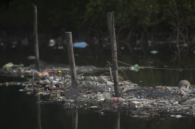 FILE - In this Feb. 28, 2015 file photo, trash floats on the water along a fence line in the Guanabara Bay in Rio de Janeiro, Brazil. The world governing body of sailing threaten Friday, April 24, 2015, to move events for the Rio 2016 Olympics out of the city's polluted Guanabara Bay unless