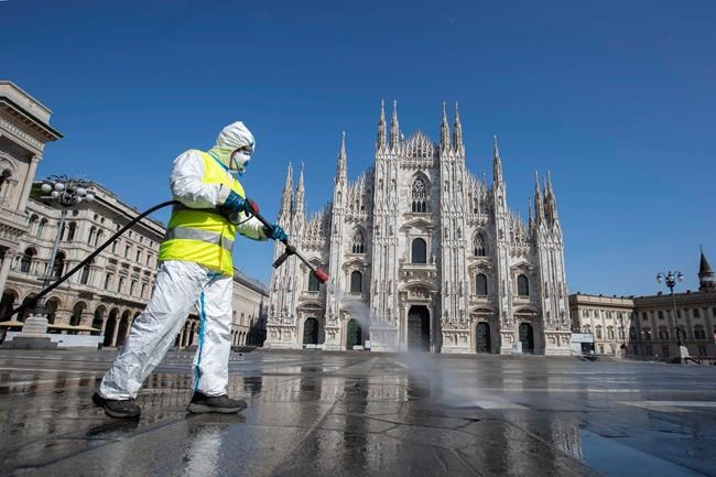 A worker sprays disinfectant to sanitize Duomo square, in downtown Milan, Italy, Tuesday, March 31, 2020. The new coronavirus causes mild or moderate symptoms for most people, but for some, especially older adults and people with existing health problems, it can cause more severe illness or death. (AP Photo/Luca Bruno)