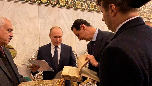 This image released by the Syrian Presidency shows Russian President Vladimir Putin, center, and Syrian President Bashar Assad, second right, during a visit to the Umayyad Mosque in Damascus, Syria, Tuesday, Jan. 7, 2020. Putin's visit is the second to the war-torn country where his troops have been fighting alongside Syrian government forces since 2015. (Syrian Presidency via AP)