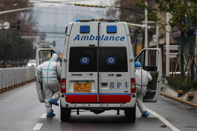 In this Sunday, Jan. 26, 2020 photo, ambulance crew members in protective gear get into their ambulance in Wuhan in central China's Hubei Province. A new viral illness being watched with a wary eye around the globe accelerated its spread in China on Sunday with 56 deaths so far, while the U.S. Consulate in the city at the epicenter announced it will evacuate its personnel and some private citizens aboard a charter flight. (Chinatopix via AP)