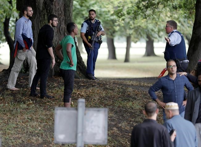 Police attempt to move people away from outside a mosque in central Christchurch, New Zealand, Friday, March 15, 2019. Many people were killed in a mass shooting at a mosque in the New Zealand city of Christchurch on Friday, a witness said. Police have not yet described the scale of the shooting but urged people in central Christchurch to stay indoors. (AP Photo/Mark Baker)