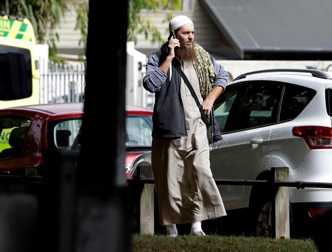 A man talks on his mobile phone across the road from a mosque in central Christchurch, New Zealand, Friday, March 15, 2019. A witness says a number of people have been killed in a mass shooting at a mosque in the New Zealand city of Christchurch; police urge people to stay indoors. (AP Photo/Mark Baker)