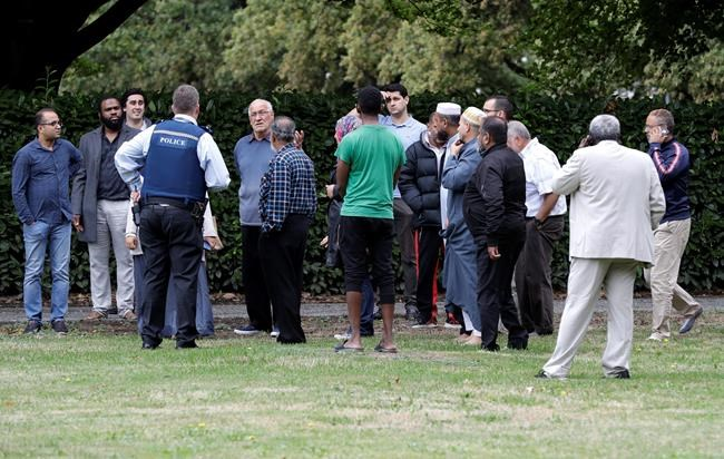 Police talk to witnesses near a mosque in central Christchurch, New Zealand, Friday, March 15, 2019. Multiple people were killed in mass shootings at two mosques full of people attending Friday prayers, as New Zealand police warned people to stay indoors as they tried to determine if more than one gunman was involved.(AP Photo/Mark Baker)
