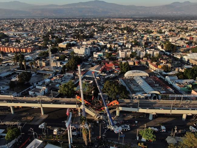 An aerial view of subway cars dangle at an angle from a collapsed elevated section of the metro, in Mexico City, Tuesday, May 4, 2021. The elevated section of Mexico City's metro collapsed late Monday killing at least 23 people and injuring at least 79, city officials said. (AP Photo/Fernando Llano)