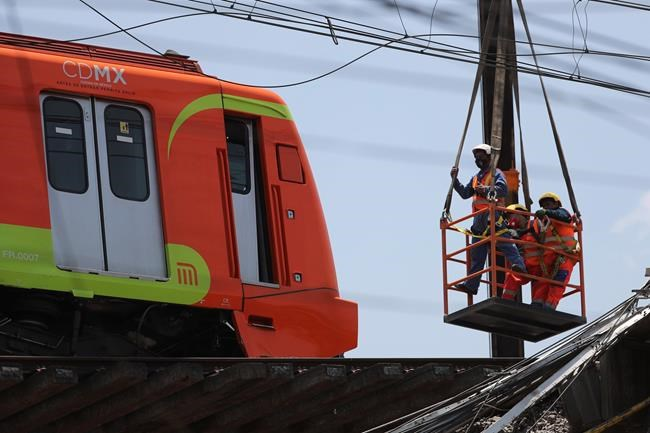 A subway car is prepared to be lowered to the ground, with the help of a crane, from a collapsed elevated section of the metro, in Mexico City, Tuesday, May 4, 2021. The elevated section of the Line 12 metro collapsed late Monday, killing at least 23 people and injuring at least 79, city officials said. (AP Photo/Marco Ugarte)