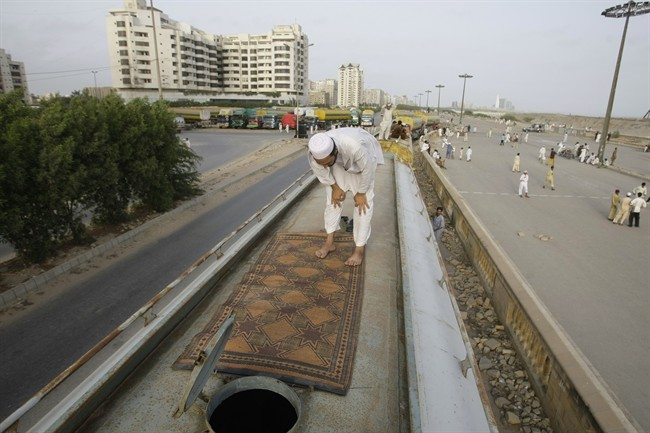 A Pakistani man prays on top of an oil tanker, which was used to transport NATO fuel supplies to Afghanistan, while parked in Karachi, Pakistan, Friday, May 25, 2012. Pakistan's parliament has unanimously approved new guidelines for the country in its troubled relationship with the United States, a decision that could pave the way for the reopening of supply lines to NATO troops in neighboring Afghanistan. (AP Photo/Fareed Khan)