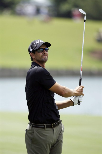 Adam Scott of Australia, reacts to his shot from the 18th fairway during the third round of The Players championship golf tournament at TPC Sawgrass, Saturday, May 10, 2014, in Ponte Vedra Beach, Fla. (AP Photo/John Raoux)