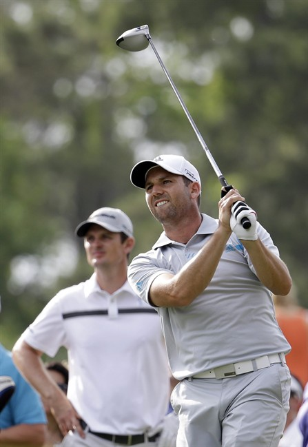 Sergio Garcia of Spain, looks at his shot from the 16th tee as Justin Rose of England waits his turn, during the third round of The Players championship golf tournament at TPC Sawgrass, Saturday, May 10, 2014 in Ponte Vedra Beach, Fla. (AP Photo/Lynne Sladky)