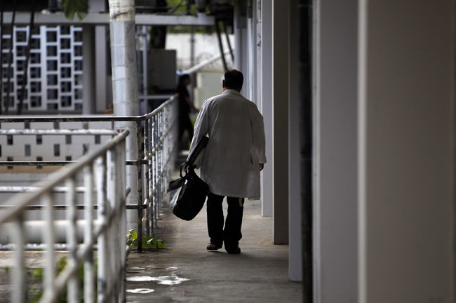 A doctor walks through a hallway at the Centro Medico trauma center in San Juan, Puerto Rico, Tuesday, April 16, 2013. A medical exodus is taking place in the Caribbean territory as doctors and nurses flee for the U.S. mainland, seeking higher salaries and better reimbursements from insurers. Many of their patients, frustrated by long waits and a scarcity of specialists, are finding they have no other choice but to follow them off the island. (AP Photo/Ricardo Arduengo)