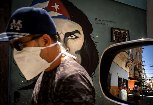"A man wearing a mask walks alongside a mural of Ernesto ""Che"" Guevara as other pedestrians are reflected in the side-view mirror of a car in Havana, Cuba, Tuesday, April 7, 2020. Cuban authorities are requiring people use masks outside their homes as a measure to help contain the spread of the new coronavirus. (AP Photo/Ramon Espinosa)"