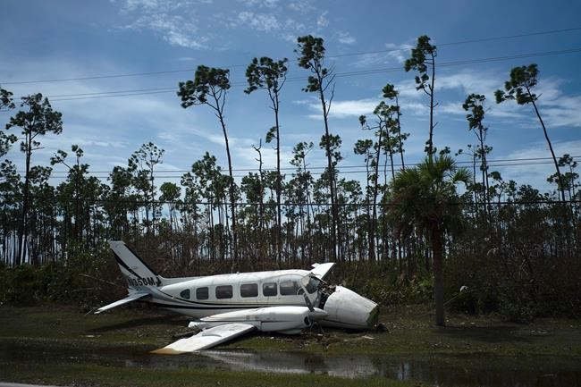 An airplane sits on the side of a road in the Pine Bay neighborhood, in the aftermath of Hurricane Dorian, in Freeport, Bahamas, Wednesday, Sept. 4, 2019. Rescuers trying to reach drenched and stunned victims in the Bahamas fanned out across a blasted landscape of smashed and flooded homes Wednesday, while disaster relief organizations rushed to bring in food and medicine. (AP Photo/Ramon Espinosa)