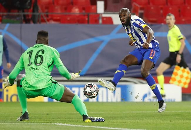 Porto's Moussa Marega, right, kicks the ball ahead of Chelsea's goalkeeper Edouard Mendy during the Champions League, first leg, quarterfinal soccer match between FC Porto and Chelsea at the Ramon Sanchez-Pizjuan stadium in Seville, Spain, Wednesday, April 7, 2021. (AP Photo/Angel Fernandez)