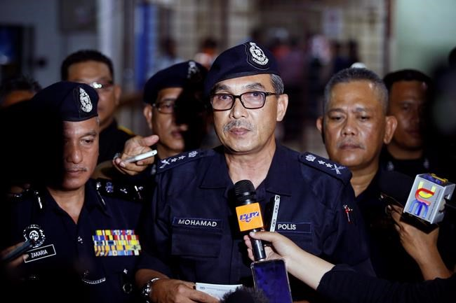 Negeri Sembilan state police chief Mohamad Mat Yusop, center, speaks to media outside a hospital morgue in Seremban, Negeri Sembilan, Malaysia, Tuesday, Aug. 13, 2019. Malaysian police say the family of missing 15-year-old London girl Nora Anne Quoirin has positively identified a body found near the nature resort where she disappeared over a week ago. (AP Photo/Lai Seng Sin)