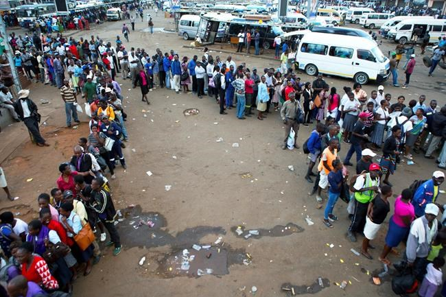 People queue for public transport in Harare, Zimbabwe, Monday, March, 23, 2020. Zimbabwe has closed its borders to non essential human traffic following its first recorded coronavirus related death. (AP Photo/Tsvangirayi Mukwazhi)