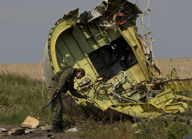 A pro-Russian rebel touches the MH17 wreckage at the crash site of Malaysia Airlines Flight 17, near the village of Hrabove, eastern Ukraine, Tuesday, July 22, 2014. A team of Malaysian investigators visited the site along with members of the OSCE mission in Ukraine for the first time since the air crash last week. (AP Photo/Vadim Ghirda)