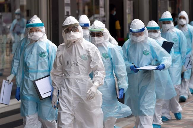 Medical workers in protective suits entering a building under lockdown in downtown Kuala Lumpur, Malaysia, on Tuesday, April 7, 2020. The Malaysian government issued a restricted movement order to the public to help curb the spread of the new coronavirus. The new coronavirus causes mild or moderate symptoms for most people, but for some, especially older adults and people with existing health problems, it can cause more severe illness or death. (AP Photo/Vincent Thian)