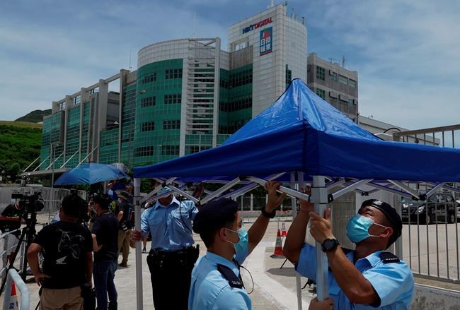 Police officers set up a tent outside the Apple Daily headquarters as Hong Kong media tycoon Jimmy Lai, who founded the local newspaper Apple Daily, was arrested by police officers at his home in Hong Kong, Monday, Aug. 10, 2020. Hong Kong police arrested Lai and raided the publisher's headquarters Monday in the highest-profile use yet of the new national security law Beijing imposed on the city after protests last year. (AP Photo/Vincent Yu)