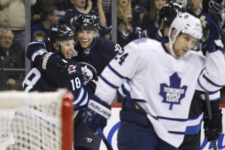 Winnipeg Jets' Bryan Little (18) and Blake Wheeler (26) celebrate the Jets' second goal against John-Michael Liles (24) and the Toronto Maple Leafs' during second-period action Tuesday. Little's goal proved to be the winner.