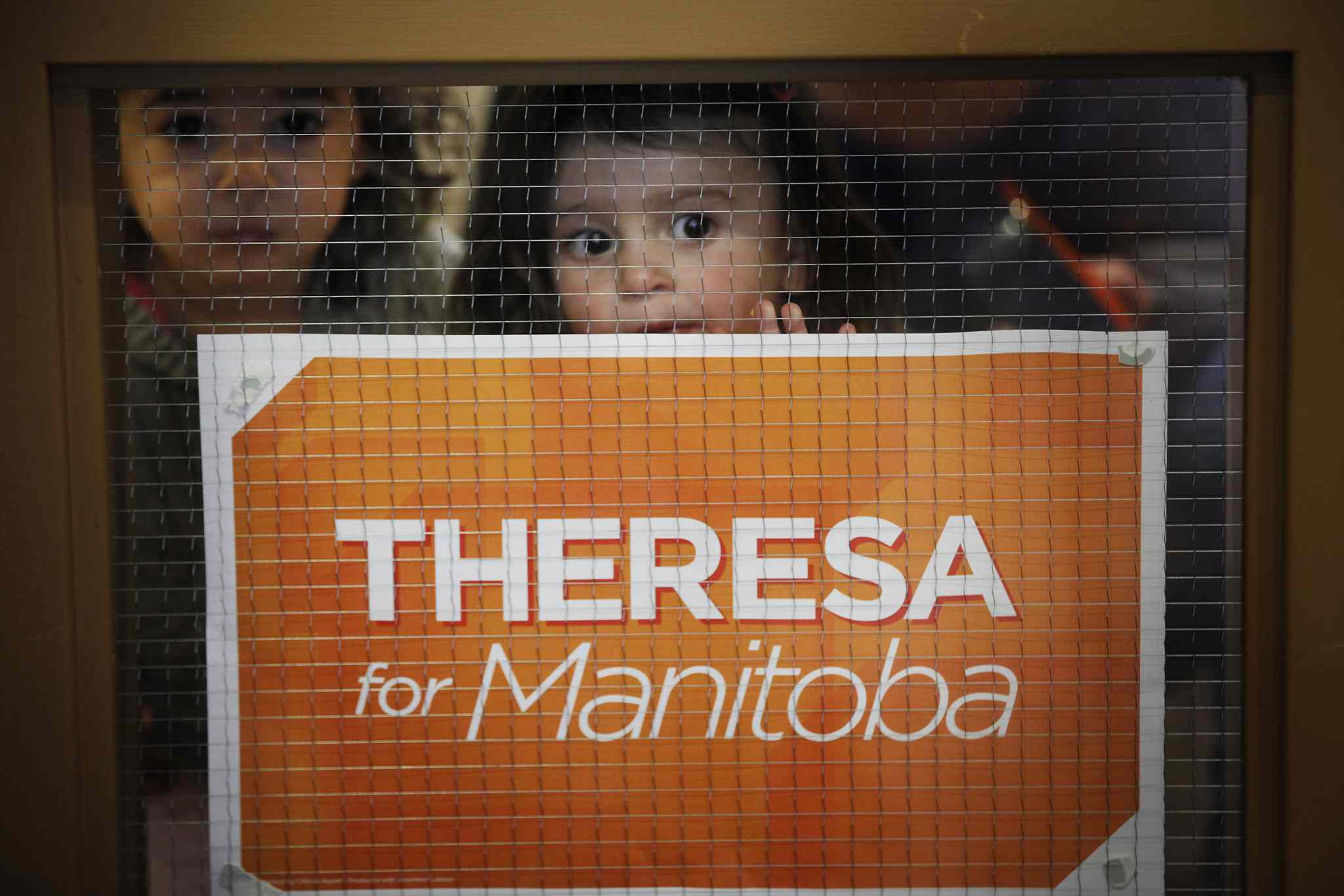 Children peek through the glass as Theresa Oswald speaks during a gathering with the Manitoba Young New Democrats Sunday.