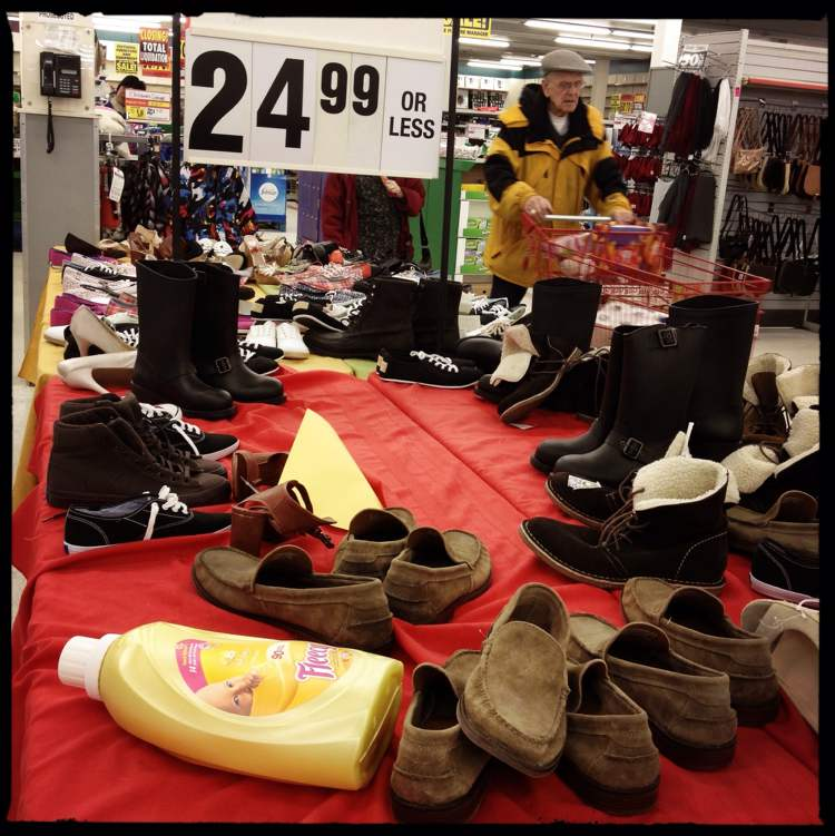 A bottle of fabric softener lays discarded on a table of discounted footwear. (Mike Deal / Winnipeg Free Press)