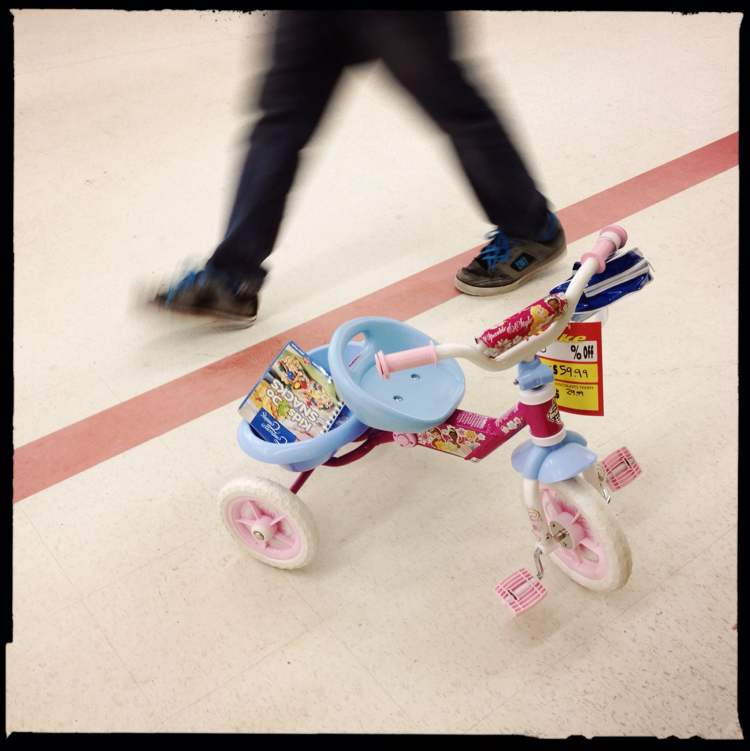 A child's tricycle sits in the middle of the isle.