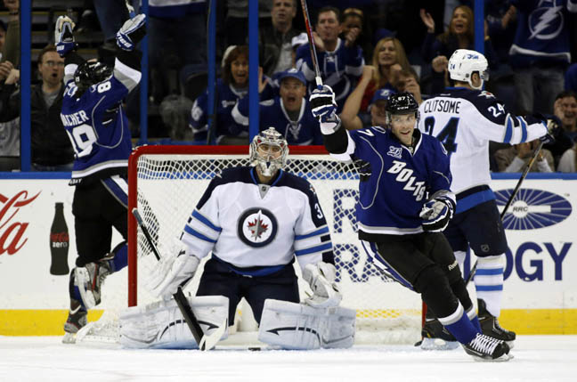 Tampa Bay's Cory Conacher (left) and Benoit Pouliot celebrate a goal as Winnipeg Jets goalie Ondrej Pavelec and defenceman Grant Clitsome resign themselves to the cruel fact.