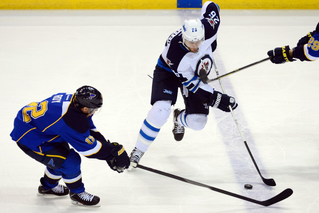 Winnipeg right-winger Blake Wheeler, right, zips past the check of Blues' centre Derek Roy during Monday night's action.