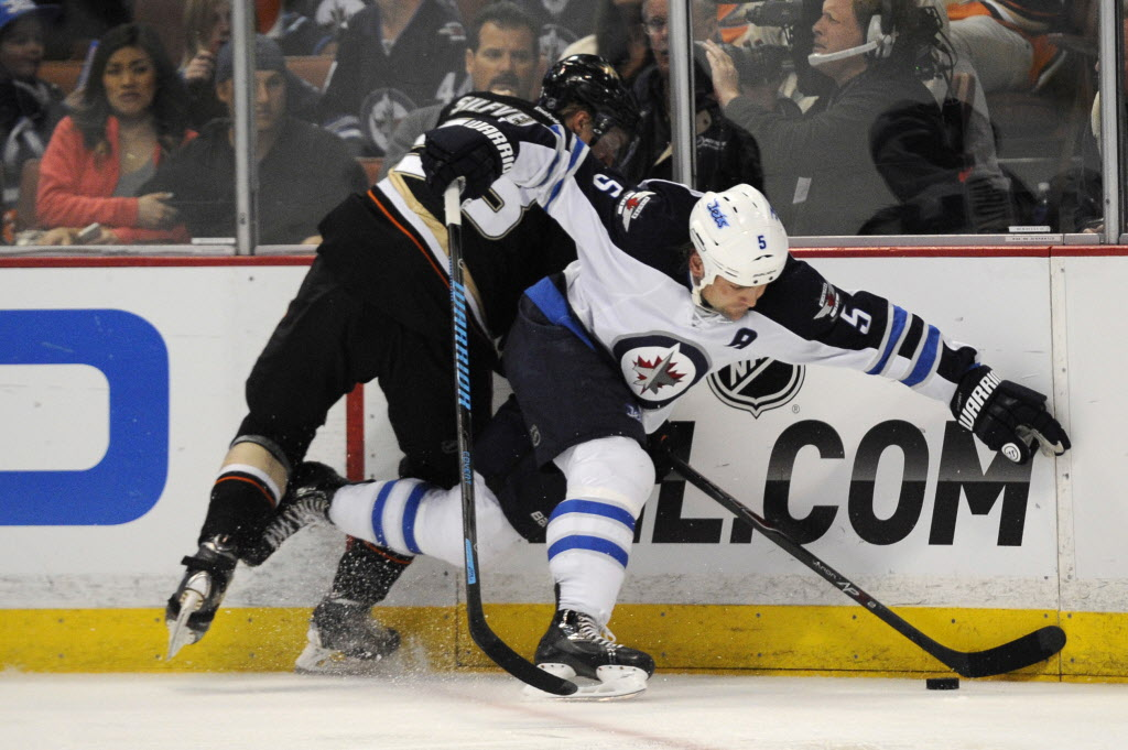 Winnipeg Jets' defenseman Mark Stuart (5) and Anaheim Ducks' right wing Jakob Silfverberg (33) battle for the puck during the second period at Anaheim's Honda Center. The Jets lost 5-4 in overtime.