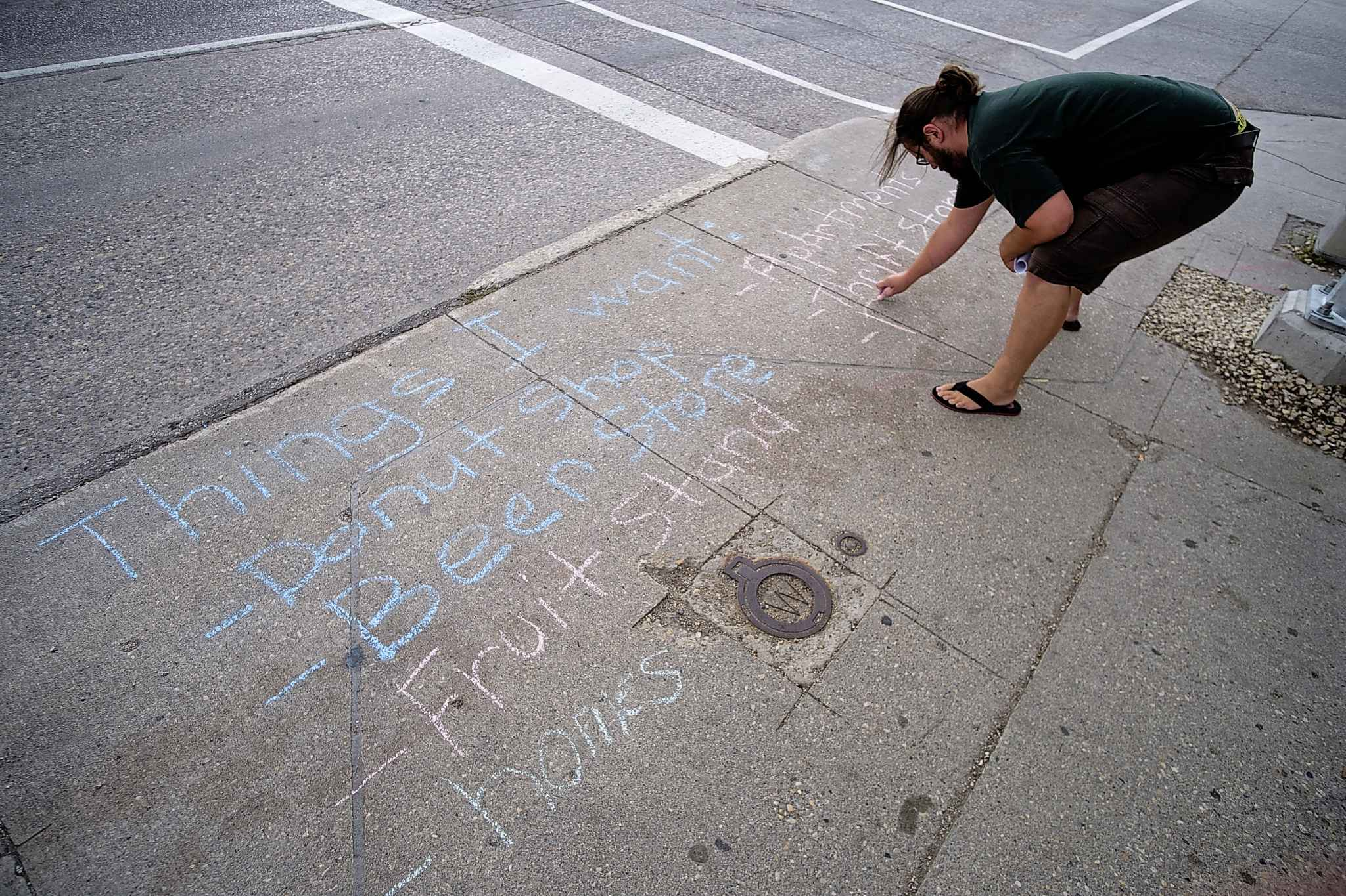 Jaret Olford, a community resident and member of the Concerned Voters Group, writes a list of ideas about what the boarded and neglected Rubin Block building could be used for during a Chalk Party, at the corner of Osborne and Morley, Wednesday.