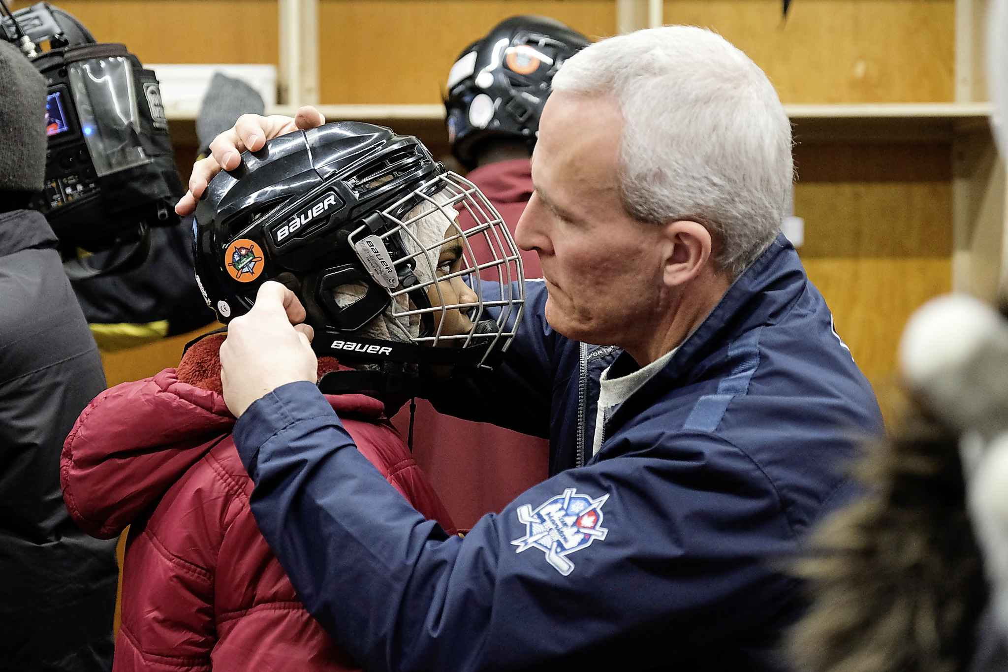 A newcomer gets a helping hand with her helmet as she gets set to go for a skate Saturday. (Daniel Crump / Winnipeg Free Press)</p>