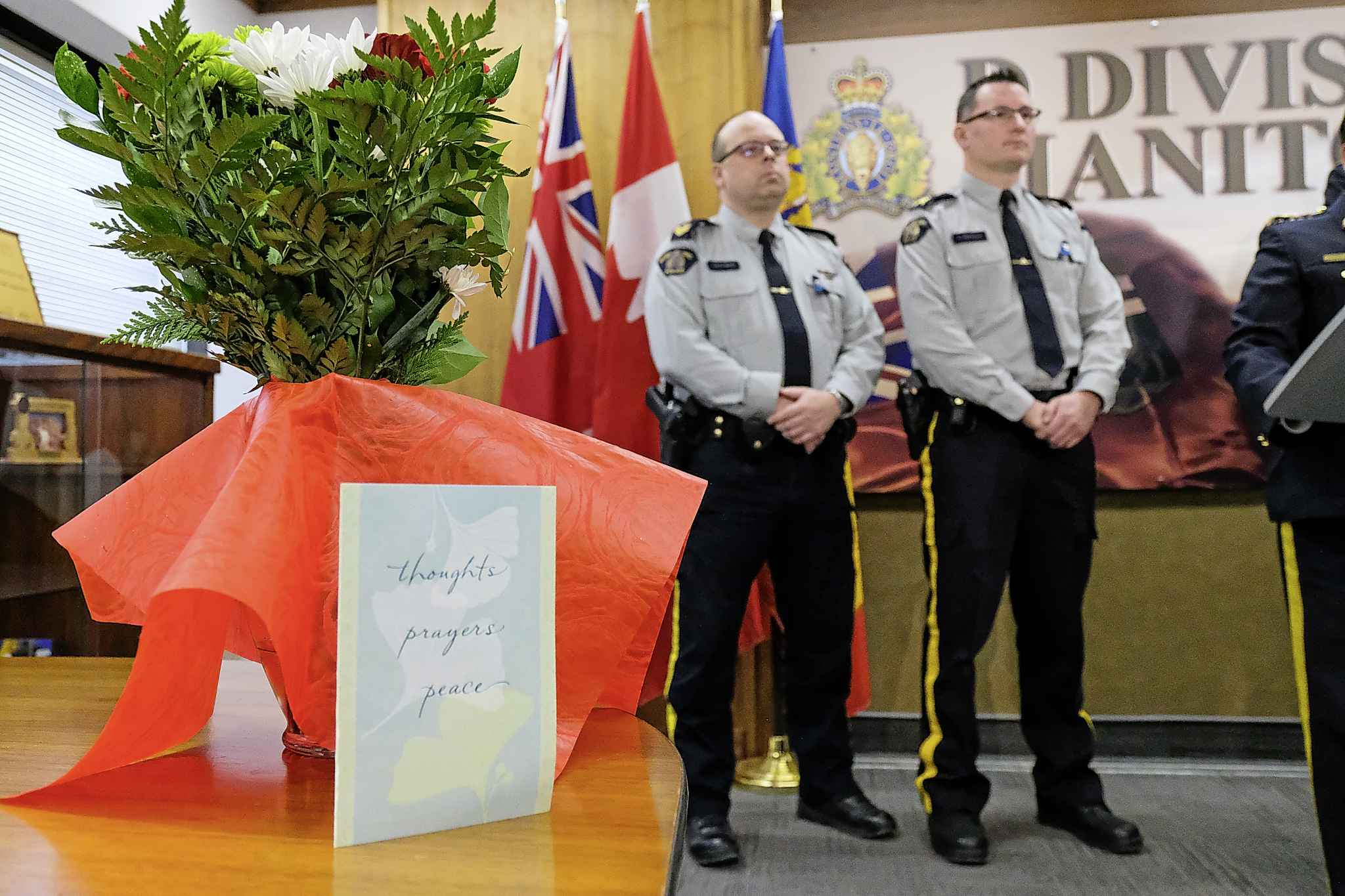 Flowers and a card sit on table at D Division Headquarters Saturday afternoon as RCMP Assistant Commissioner Jane MacLatchy provides details about the death of Const. Allan Poapst. (Daniel Crump / Winnipeg Free Press)