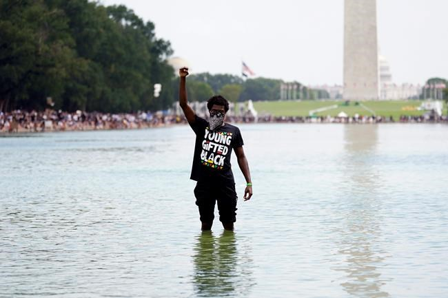 """A man stands in the Reflecting Pool as people attend the March on Washington, Friday Aug. 28, 2020, in Washington, on the 57th anniversary of the Rev. Martin Luther King Jr.'s """"I Have A Dream"""" speech. (AP Photo/Carolyn Kaster)"""