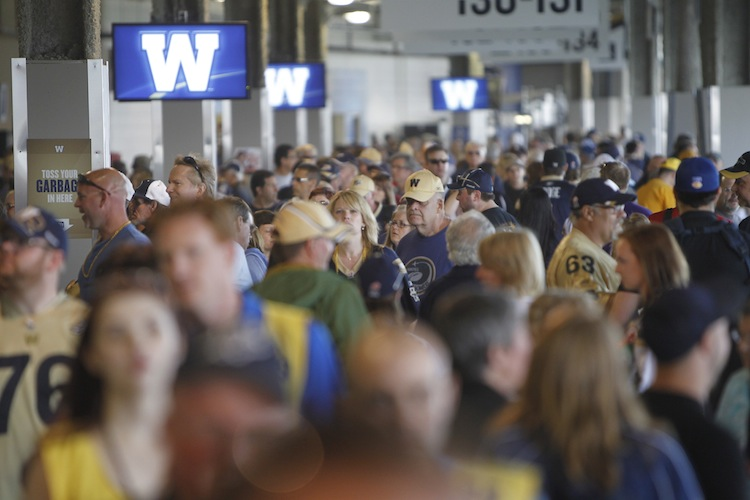 Fans mill about the concourse level at Investors Group Field before kickoff.