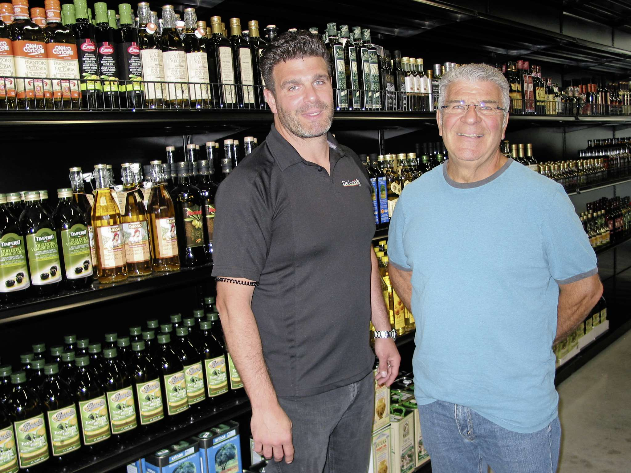 (From left) Marco De Luca and his father Peter stand next to the shelves holding the wide variety of oils available at the company's new location at 66 South Landing in the RM of Macdonald.