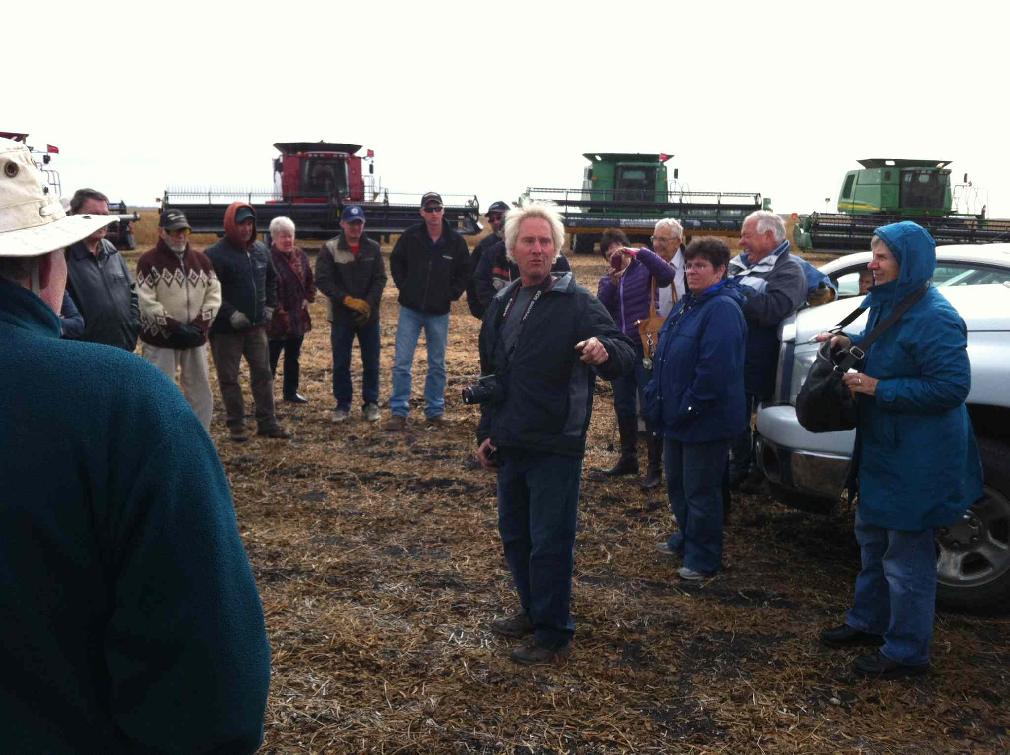 Starbuck farmer Dave Wiebe (centre) talks to those attending last fall's harvest done on behalf of the Canadian Foodgrains Bank.