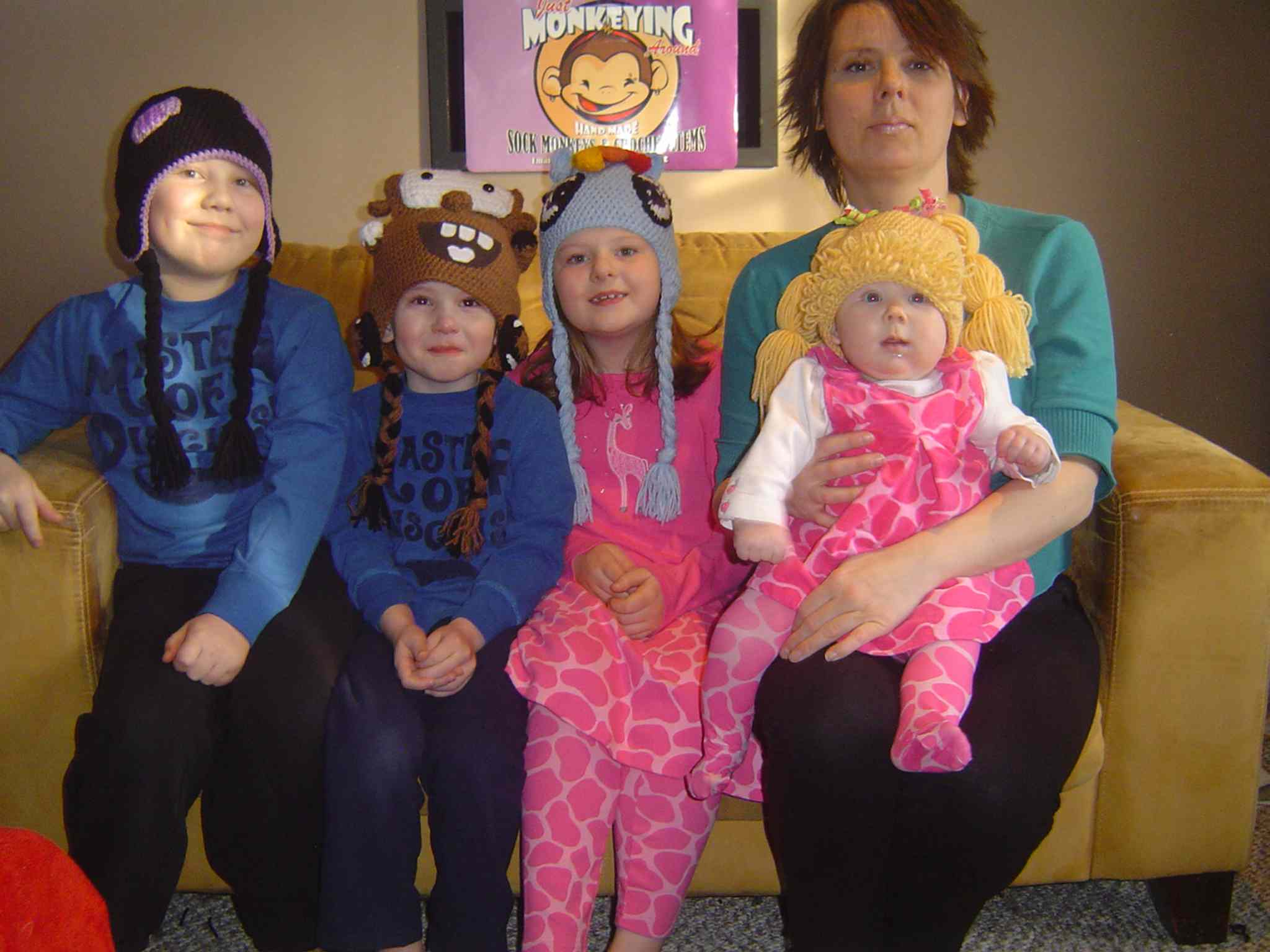Michelle Ducharme holds daughter Evelyn, with children (left) William, Richard and Katherine, all wearing hats designed and crocheted by Michelle.