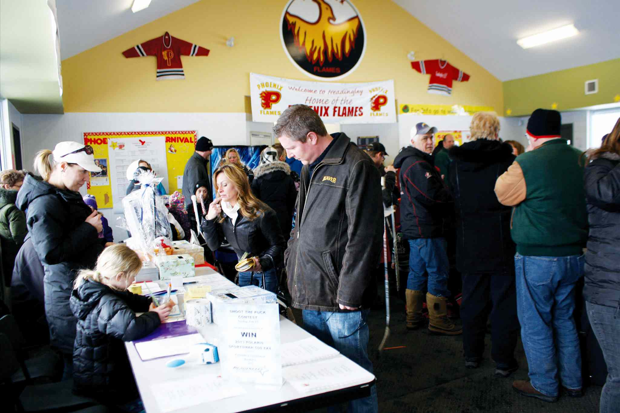 The silent auction at the 2013 Phoenix Winter Carnival drew lots of interest. This year's prizes have been donated by local businesses to support programming at the Phoenix Community Centre.