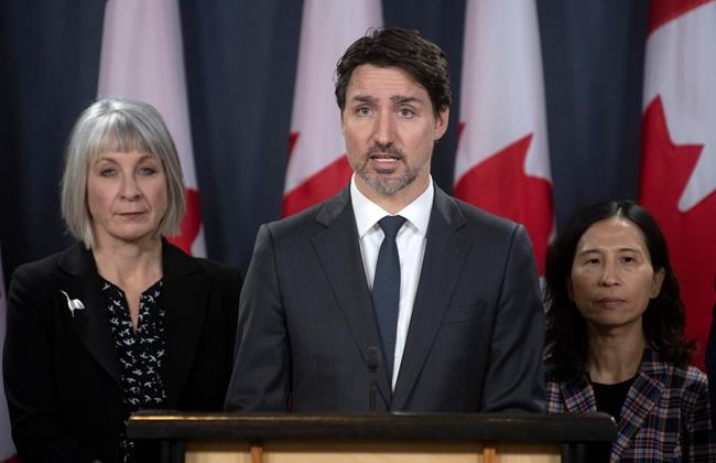 Minister of Health Patty Hajdu and Chief Medical Officer Theresa Tam (right) look on as Prime Minister Justin Trudeau responds to a question during a news conference on the coronavirus situation, in Ottawa, Wednesday, March 11, 2020. THE CANADIAN PRESS/Adrian Wyld
