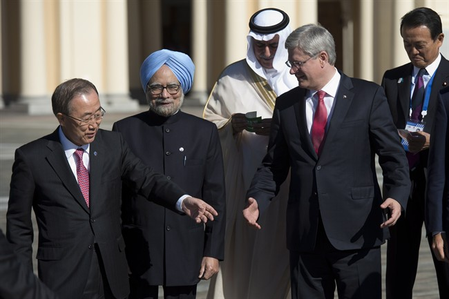 Indian Prime Minister Manmohan Singh (centre) looks on as Canadian Prime Minister Stephen Harper and United Nations Secretary General Ban Ki-Moon talk about where they are supposed to stand as the Finance Ministers from Saudia Arabia Ibrahim bin Abdulaziz Al-Assaf and Japan Taro Aso (back right) wait for the other leaders during the family photo at the G20 Summit Friday September 6, 2013 in St.Petersburg, Russia. THE CANADIAN PRESS/Adrian Wyld