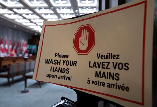 A sign outside a news conference reminds everyone to wash their hands as they enter the room in Ottawa, Tuesday April 14, 2020. THE CANADIAN PRESS/Adrian Wyld