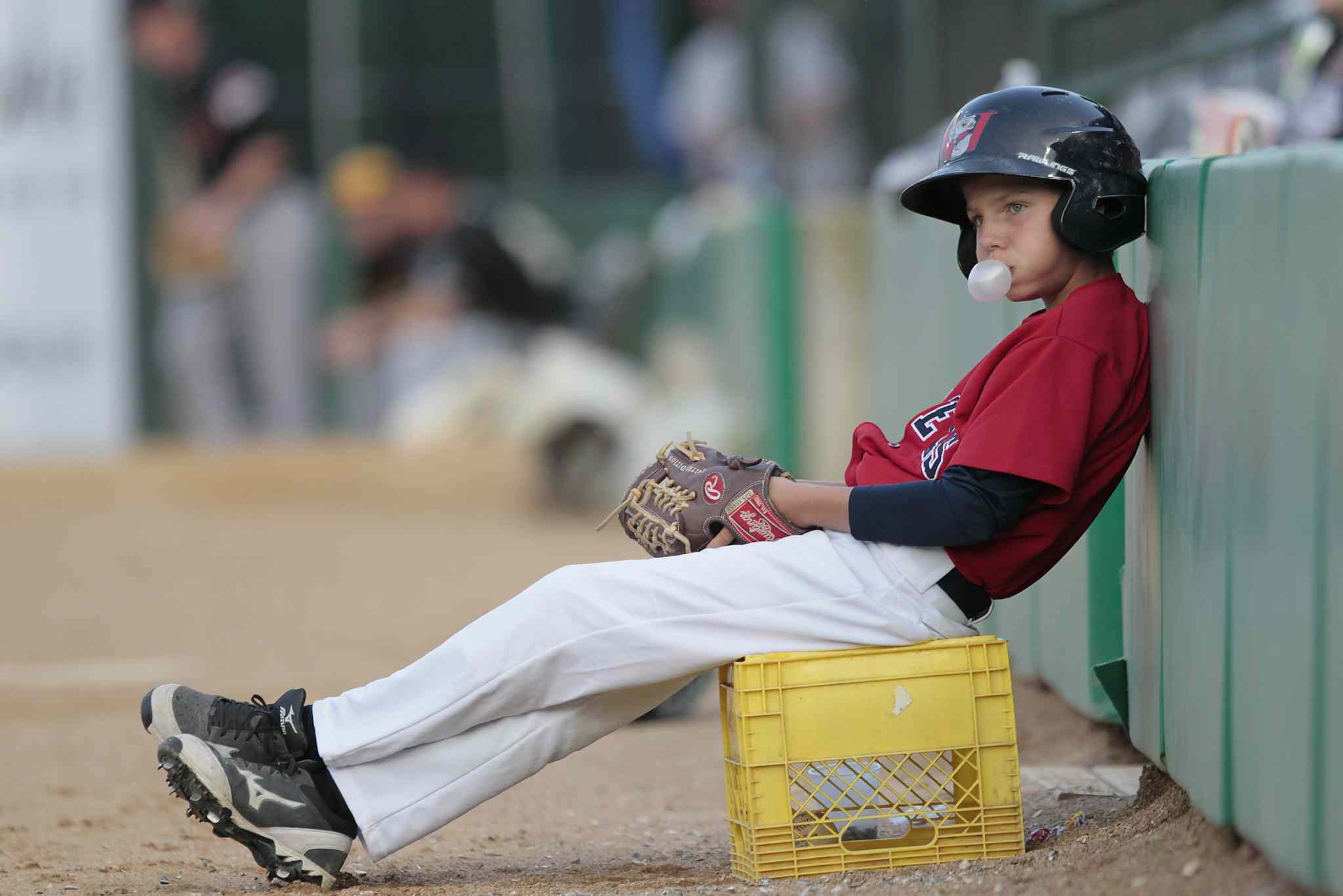 A ball-boy settles in to watch the 2014 American Association All-Star game.