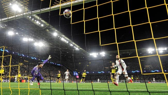 PSG's Neymar, right, scores against Dortmund's goalkeeper Roman Buerki during the Champions League round of 16 first leg soccer match between Borussia Dortmund and Paris Saint Germain in Dortmund, Germany, Tuesday, Feb. 18, 2020. (AP Photo/Martin Meissner)