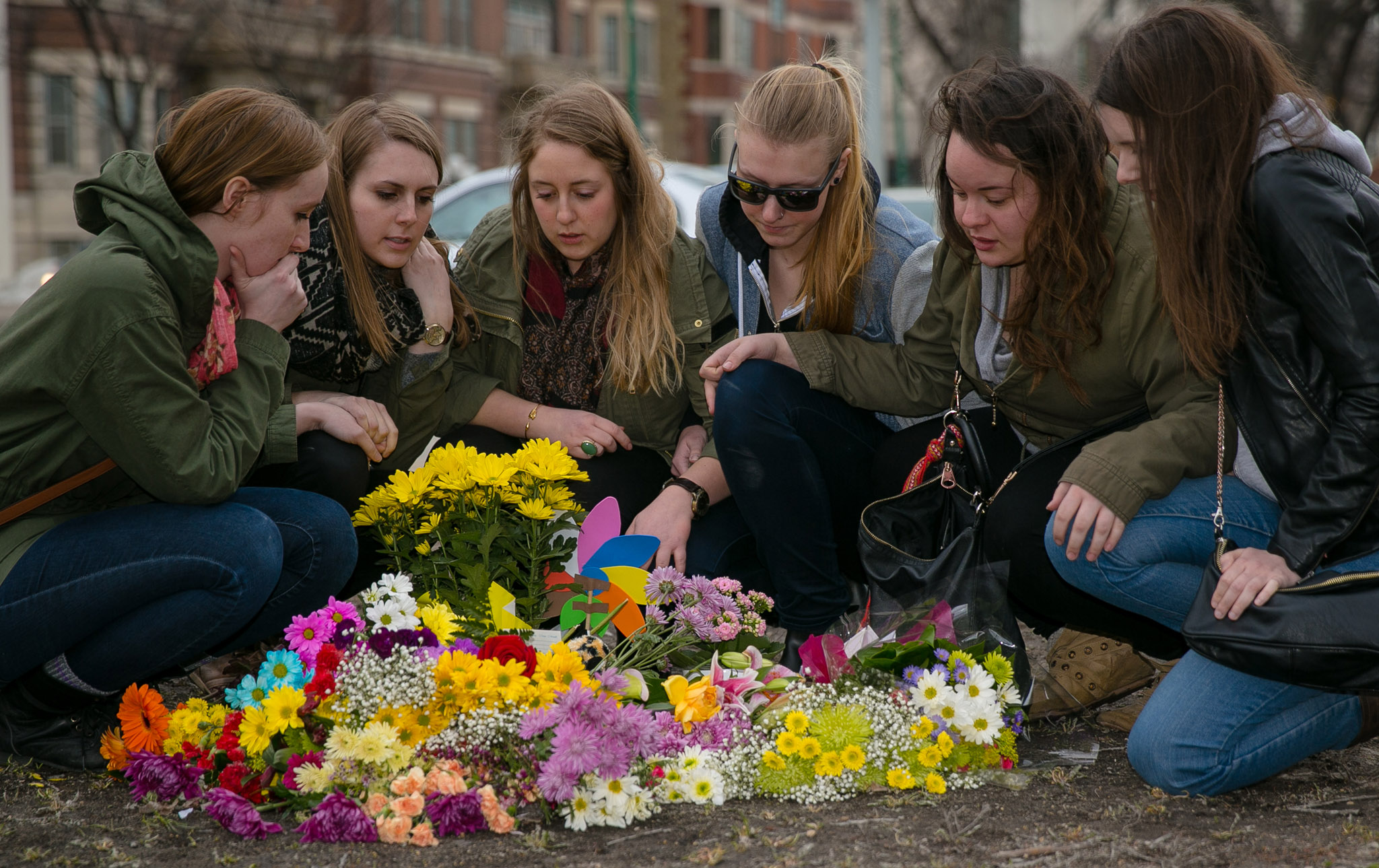 Kayla Prokopchuk (third from left) is surrounded by childhood friends of Amy Gilbert at a memorial of flowers on Broadway at Donald Street. Gilbert, 23, was struck and killed at the intersection Saturday afternoon. The group of friends have known each other since Grade 7. From left to right, Megan Dudeck, Michelle Ewacha, Kayla Prokopchuk, Meredith Stoesz, April Saurette, Angela Harris.